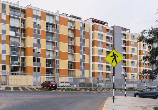 Желто-оранжевые здания и желтый знак пешеходного движения на переднем плане