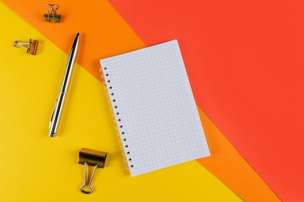 Желтый и оранжевый стол офисного стола с пустой тетрадью и другими канцелярскими принадлежностями. вид сверху с копией пространства, плоская планировка.