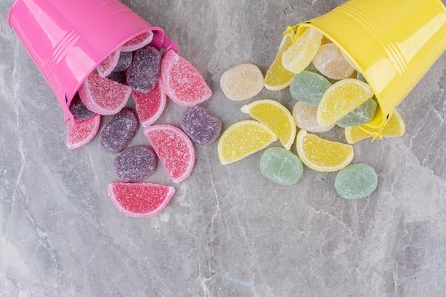 Желтые и розовые ведра с сахарным мармеладом на мраморном фоне.