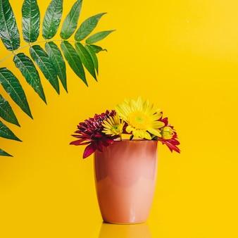 Желтые и розовые цветы герберы в розовой чашке на желтом фоне с зеленой большой зеленой веткой с листьями