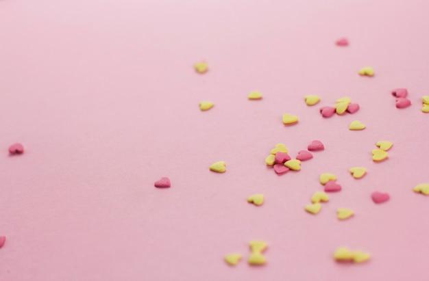 Желтый и розовый в форме сердца кондитерские конфетти на розовом фоне копией пространства.
