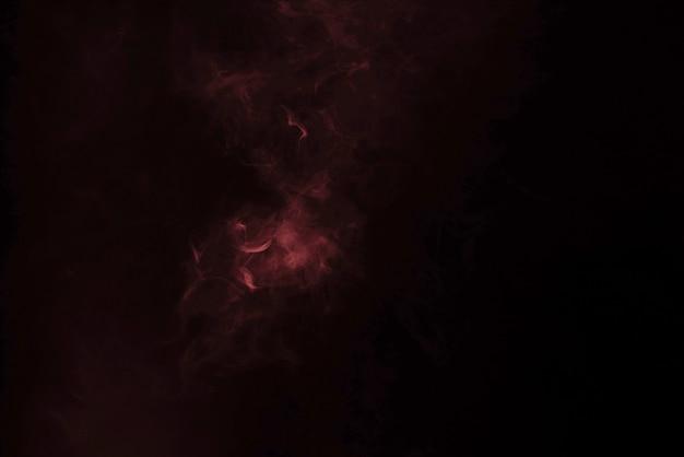 黒い表面に黄色とピンクの蒸気。スペースをコピーします。