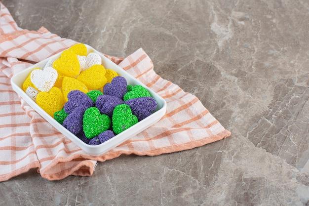 Желтые и фиолетовые конфеты в твердой форме внутри белой тарелки.
