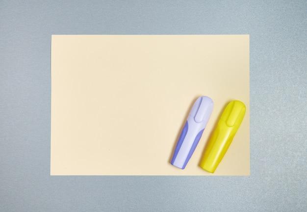 Желтые и фиолетовые маркеры на желтом листе бумаги на сером фоне. плоская планировка. вид сверху