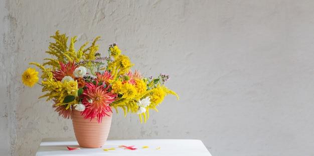 빈티지 선반에 꽃병에 노란색과 빨간색 꽃