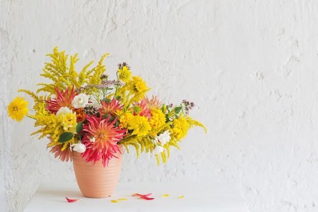 Желтые и красные цветы в вазе на винтажной полке