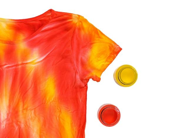 黄色と赤のペンキの瓶とタイダイのtシャツを白で隔離