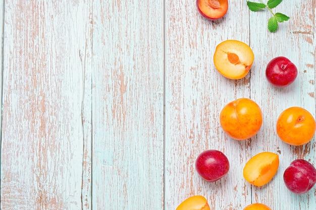 着用した木製のテーブルフラットレイ、秋の果物のコンセプト、コピースペースに黄色と赤のプラム