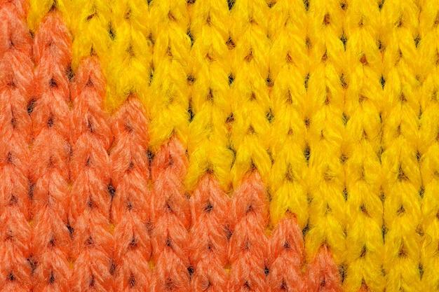 Желтая и красная синтетическая трикотажная ткань заделывают. вязаная ткань текстуры фона