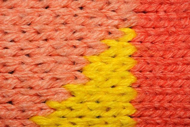 노란색과 빨간색 합성 니트 직물을 닫습니다. 니트 직물 질감 배경