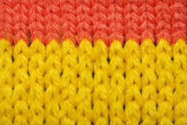 노란색과 빨간색 합성 니트 직물을 닫습니다. 니트 패브릭 질감. 여러 가지 빛깔의 패턴 니트 패브릭 질감. 배경