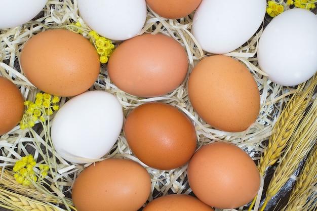 黄色と白の卵、花、麦わら