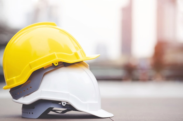 햇빛과 도시에 콘크리트 바닥에 건물 건설 현장에서 프로젝트에서 노란색과 흰색 하드 안전 헬멧 모자를 착용. 엔지니어 또는 작업자로 노동자를위한 헬멧. 개념 안전 제일.