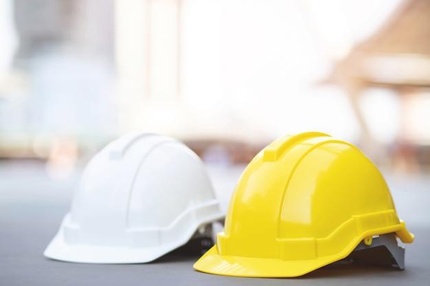 햇빛과 콘크리트 바닥에 건물 건설 현장에서 프로젝트에서 노란색과 흰색 하드 안전 헬멧 모자를 착용하십시오. 엔지니어 또는 작업자로 노동자를위한 헬멧. 개념 안전 제일.