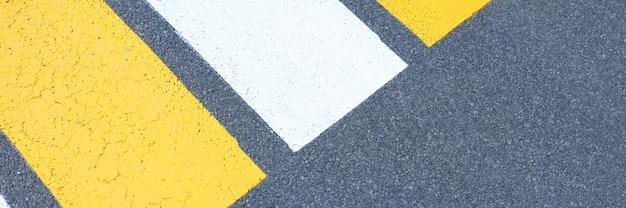 Желтые и белые полосы пешеходного перехода нарисованы на асфальтовом фоне.