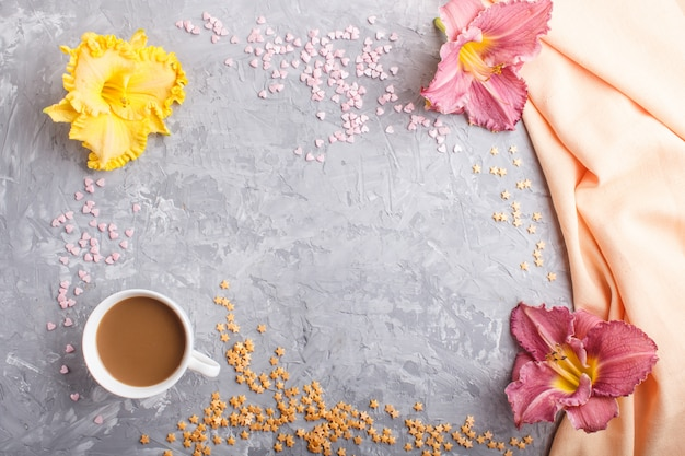 Yellow anf purple day-lilies cup of coffee, with orange textile. top view, background copyspace.