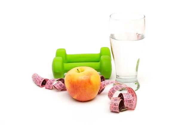黄リンゴと緑のダンベル、白いテーブルに分離された水のガラスを巻尺