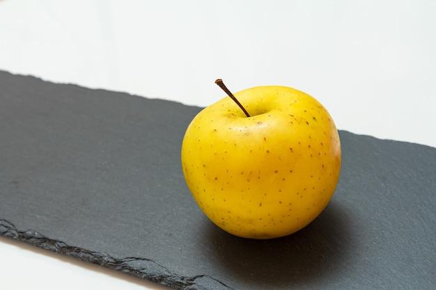黒い石のボードと白い背景の上の黄色いリンゴの果実。有機フルーツ。