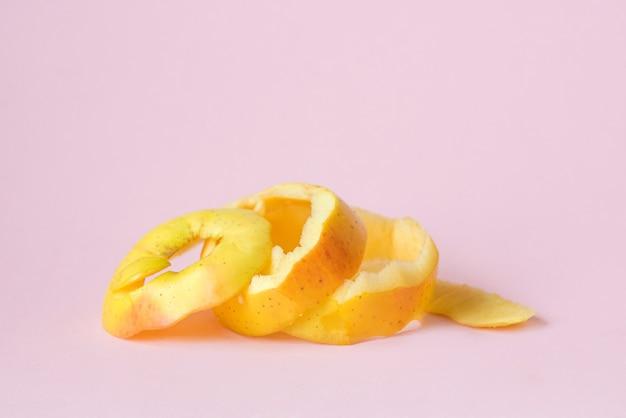 循環経済のリサイクルのシンボルとしてピンクの背景に黄色いリンゴの皮