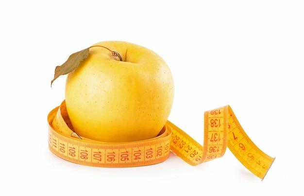 白い背景で隔離の測定テープと黄色いリンゴ。