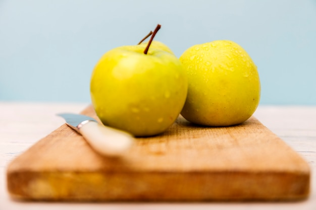 Yellow apple on wooden desk. green apple and knife on wooden table.