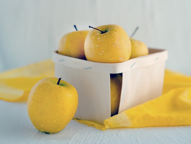 흰색 배경에 바구니에 노란색 사과 건강한 영양에 대한 상징적 이미지 개념