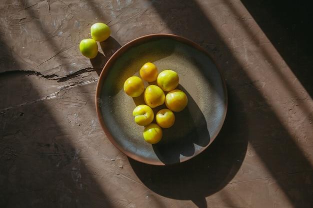 Желтые яблоки в тарелку и рядом вид сверху на фактурном столе