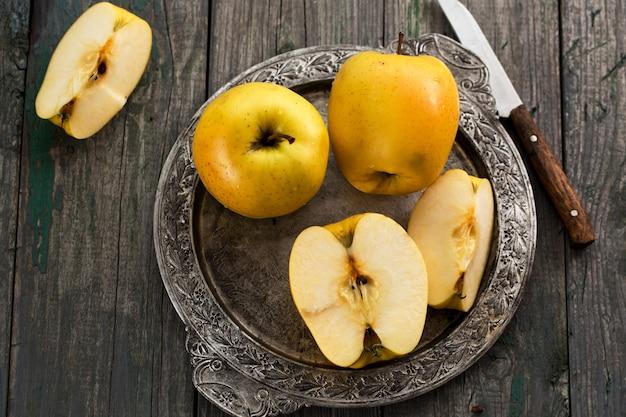 Желтые яблоки на металлическом подносе в деревенском стиле