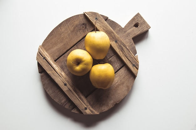 Yellow apples on a sliced board in vintage style. leaves, food, wholesome food, vegan, farm product.