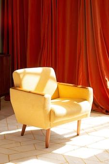 黄色のアームチェアは、オレンジ色の布の壁の背景のカーペットの上に立っています。