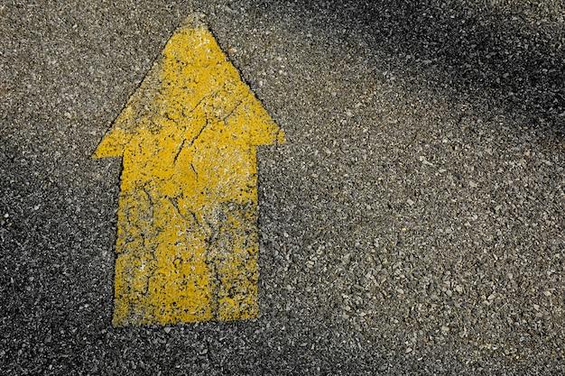 Yellow arrow painted on asphalt road