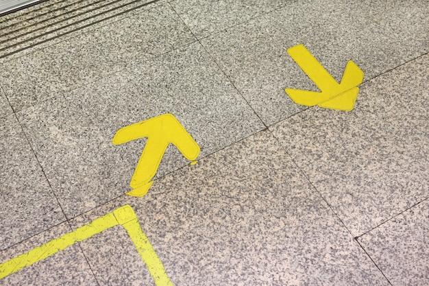 Желтой стрелкой знак обозначить на мраморном полу, на метро.