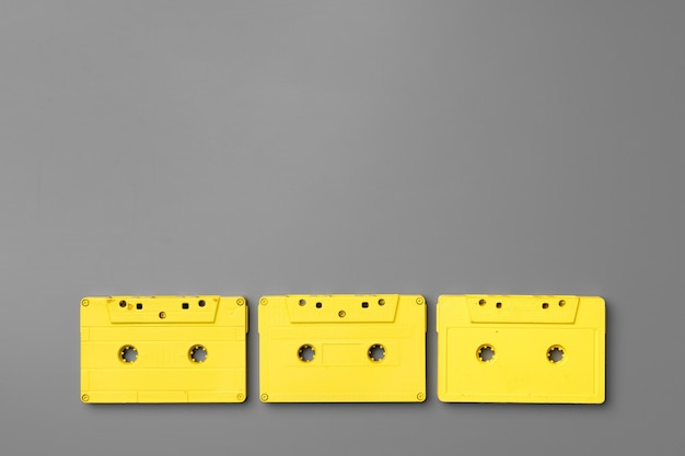 Yellow audio cassettes on gray background top view, copy space