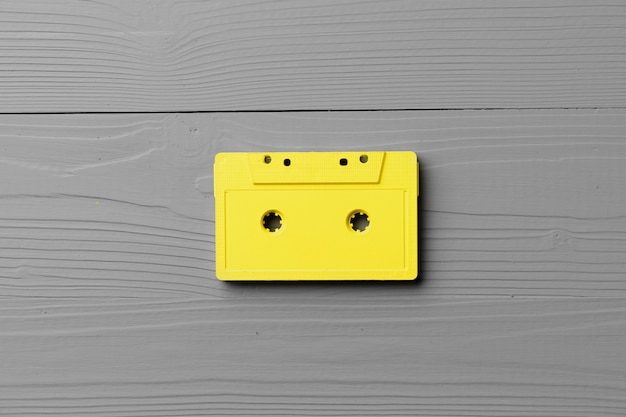 Yellow audio cassettes on gray surface top view