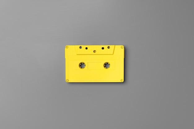灰色の背景上面図、コピースペースに黄色のオーディオカセット