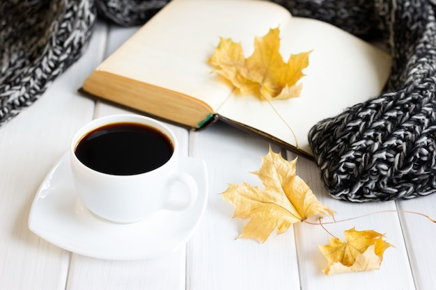 Yellow autumn leaves coffee cup warm knitted scarf with opened old book on wooden boards