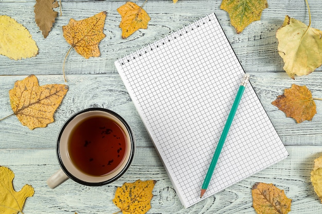 Yellow autumn leaves, a cup of tea and a notebook on a light old wooden background