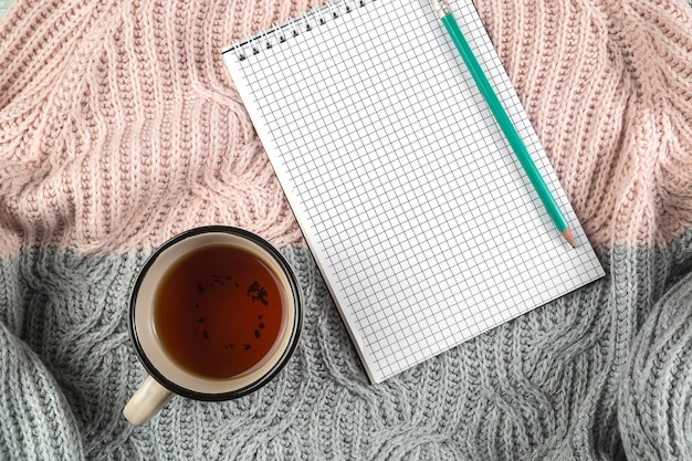 Yellow autumn leaves, a cup of tea and a notebook on a textured sweater