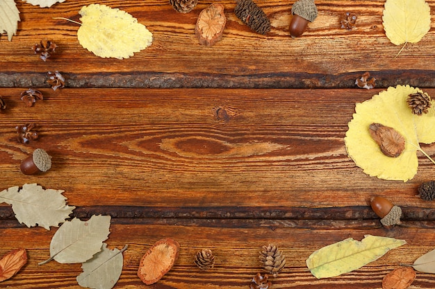 Yellow autumn leaves on a dark old wooden background with a blank space for text