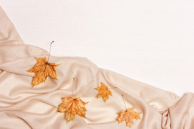 노란 단풍 플랫 복사 공간 흰색 나무 배경에 누워. 단풍 나무와 아늑한 따뜻한 팔 라틴, 가을 테마의 자연 잎.