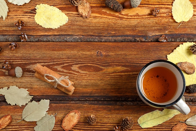 Yellow autumn leaves and a glass of tea on a dark old wooden background with a blank space for text