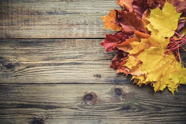Yellow autumn leaves on wooden background with copyspace