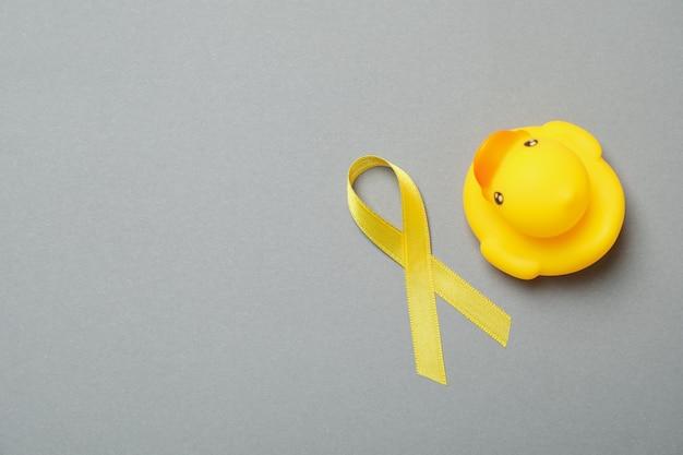 Желтая информационная лента и резиновая утка на сером