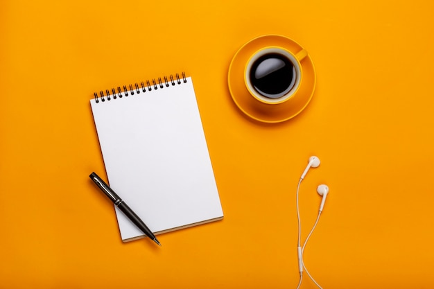 On a yellow background, a cup of black coffee with a notepad and headphones