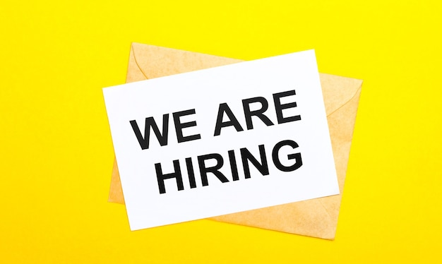 On a yellow background, an envelope and a card with the text we are hiring. view from above