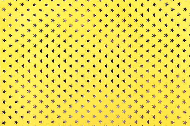 Yellow background from metal foil paper with a golden stars