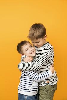 서로 포옹하는 작은 귀여운 유아 형제의 노란색 배경 스튜디오 사진. 형제 사랑 개념.