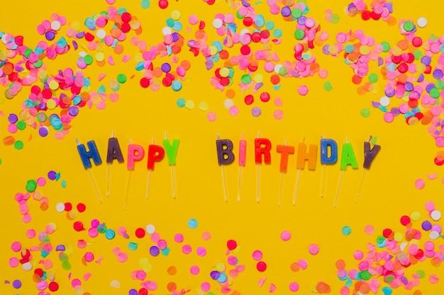 Yellow background with confetti and the letters