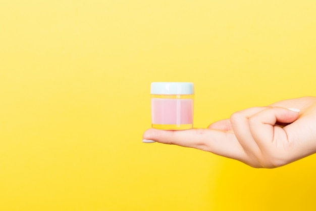 Yellow background with female hand holding cosmetics jar and copy space for your design