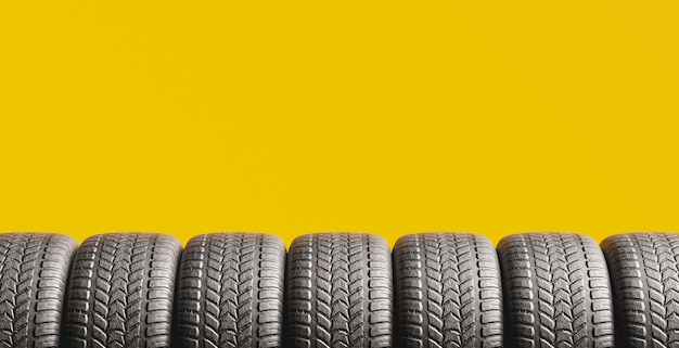 Yellow background with tires peeking out from the bottom and space for text. 3d rendering